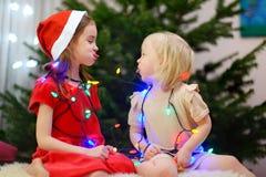 Deux petites soeurs adorables décorant un arbre de Noël Photo stock