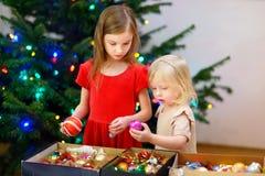 Deux petites soeurs adorables décorant un arbre de Noël Photos stock