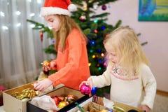 Deux petites soeurs adorables décorant un arbre de Noël Photographie stock libre de droits