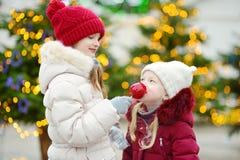 Deux petites soeurs adorables mangeant les pommes rouges couvertes de glaçage de sucre sur le marché traditionnel de Noël Photos stock