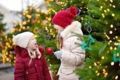 Deux petites soeurs adorables mangeant les pommes rouges couvertes de glaçage de sucre sur le marché traditionnel de Noël Images libres de droits