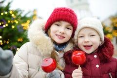 Deux petites soeurs adorables mangeant les pommes rouges couvertes de glaçage de sucre sur le marché traditionnel de Noël Image libre de droits