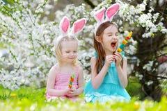 Deux petites soeurs adorables mangeant les sucreries colorées de gomme sur Pâques Photographie stock libre de droits