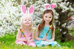 Deux petites soeurs adorables mangeant les sucreries colorées de gomme sur Pâques Image stock