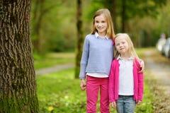 Deux petites soeurs adorables riant et étreignant le jour chaud d'été en parc Photo stock