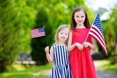 Deux petites soeurs adorables tenant les drapeaux américains dehors le beau jour d'été Image stock