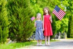 Deux petites soeurs adorables tenant les drapeaux américains dehors le beau jour d'été Photographie stock