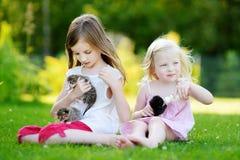 Deux petites soeurs alimentant des chatons avec du lait Photos libres de droits