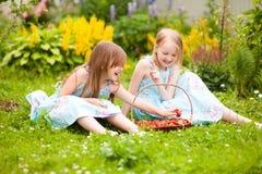 Deux petites soeurs avec le panier plein des fraises organiques dans t Images stock