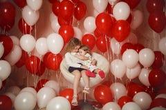 Deux petites soeurs avec les ballons rouges et blancs Photographie stock libre de droits