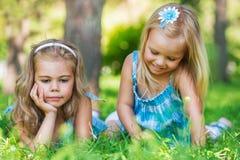 Deux petites soeurs ayant l'amusement dans le parc d'été Image stock