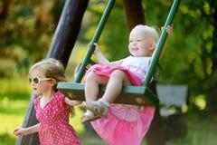 Deux petites soeurs ayant l'amusement sur une oscillation Images stock