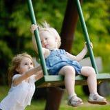 Deux petites soeurs ayant l'amusement sur une oscillation Photographie stock libre de droits