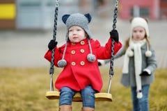Deux petites soeurs ayant l'amusement sur une oscillation Image libre de droits