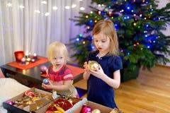 Deux petites soeurs décorant un arbre de Noël Images stock