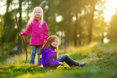 Deux petites soeurs drôles ayant l'amusement pendant la hausse de forêt le beau jour d'automne dans les Alpes italiens Photographie stock libre de droits