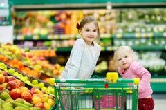 Deux petites soeurs faisant des emplettes dans un magasin de nourriture Images libres de droits