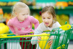 Deux petites soeurs faisant des emplettes dans un magasin de nourriture Photos libres de droits