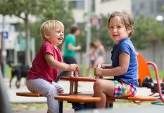 Deux petites soeurs heureuses sur le conseil de balancement Image stock