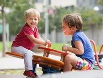 Deux petites soeurs heureuses sur le conseil de balancement Photographie stock libre de droits