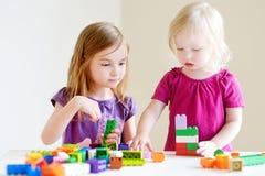 Deux petites soeurs jouant avec les blocs colorés photographie stock