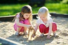 Deux petites soeurs jouant dans un bac à sable photo stock