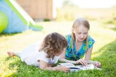 Deux petites soeurs lisant dehors dans le jour d'été Image libre de droits