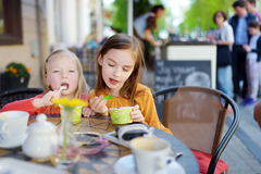 Deux petites soeurs mangeant la crème glacée dans un café extérieur Photo stock