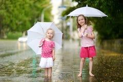 Deux petites soeurs mignonnes ayant l'amusement sous une pluie Photos stock
