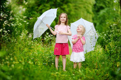 Deux petites soeurs mignonnes ayant l'amusement sous une pluie Image stock