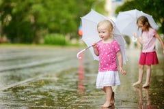 Deux petites soeurs mignonnes ayant l'amusement sous une pluie Photographie stock libre de droits