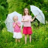 Deux petites soeurs mignonnes ayant l'amusement sous une pluie Photographie stock