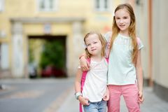Deux petites soeurs mignonnes ayant une promenade ensemble dans une ville le jour chaud d'été Image libre de droits
