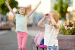 Deux petites soeurs mignonnes ayant une promenade ensemble dans une ville le jour chaud et ensoleillé d'été Images stock