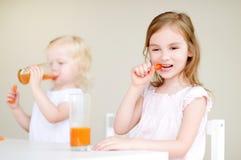 Deux petites soeurs mignonnes buvant du jus de carotte Photographie stock