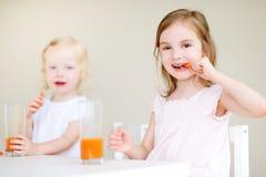Deux petites soeurs mignonnes buvant du jus de carotte Photos stock