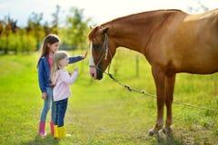 Deux petites soeurs mignonnes choyant un cheval dans la campagne Photographie stock