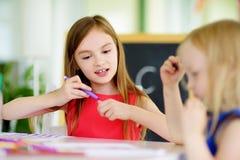 Deux petites soeurs mignonnes dessinant avec les crayons colorés à une garde Enfants créatifs peignant ensemble Photographie stock libre de droits