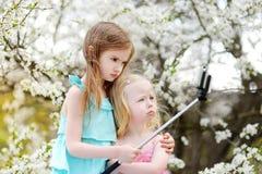 Deux petites soeurs mignonnes prenant une photo de lui-même avec un bâton de selfie Photo stock