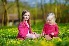 Deux petites soeurs mignonnes sur le gisement de fleur de floraison Image libre de droits