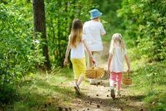 Deux petites soeurs mignonnes trimardant dans une forêt avec leur grand-mère le beau jour d'été Photos stock