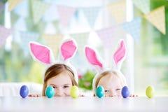 Deux petites soeurs mignonnes utilisant des oreilles de lapin jouant l'oeuf chassent sur Pâques Photographie stock libre de droits