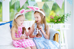 Deux petites soeurs mignonnes utilisant des oreilles de lapin mangeant des lapins de Pâques de chocolat Images stock