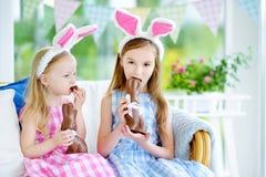 Deux petites soeurs mignonnes utilisant des oreilles de lapin mangeant des lapins de Pâques de chocolat Photographie stock libre de droits