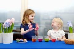 Deux petites soeurs peignant des oeufs de pâques Photographie stock libre de droits