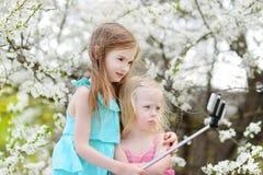Deux petites soeurs prenant une photo de lui-même Photographie stock libre de droits