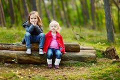Deux petites soeurs reposant sur un identifiez-vous une forêt image stock