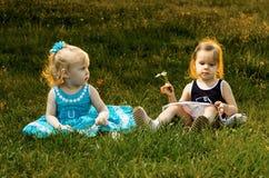 Deux petites soeurs s'asseyant dans l'herbe Photos libres de droits