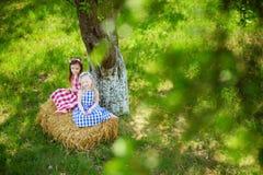 Deux petites soeurs s'asseyant sur une meule de foin dans le pommier font du jardinage le jour ensoleillé d'été Photographie stock libre de droits