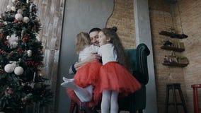 Deux petites soeurs se sont habillées dans des vêtements identiques une nuit de Noël courent joyeux à son père qui s'assied dans  clips vidéos